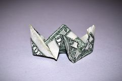 Big ship - great diving... A dollar bill folded into a paper boat on white background stock image