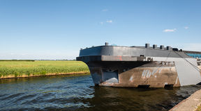Big ship in a narrow canal surrounded by a rural landscape Royalty Free Stock Image