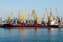 Big ship in the port on the background of yellow wagons and containers. Big ship in the port on the background of yellow wagons and containers. Horizontal frame Stock Photos