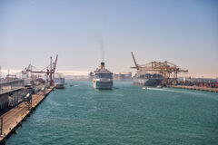 Big ships enter sea port. Barcelona, Spain - March 30, 2016: big ships or ocean liners marine vessels enter port on beautiful blue sea water on sunny day on Stock Photo