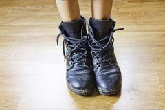 Big shoes. On a little feet on wood floor Royalty Free Stock Photography