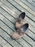 Big Shoes. Dad's well-worn, much-loved, and hard-to-fill shoes against a weathered wood background royalty free stock image