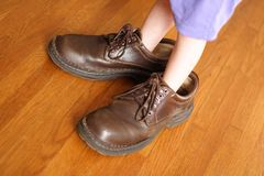 Big Shoes to Fill. Little girl standing in her daddy's shoes Stock Photo