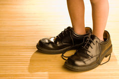 Big shoes to fill, child's feet in large black shoes. Big shoes to fill, child's feet in large grown-up black shoes, on backlit wood floor, playing dress-up Stock Photo
