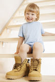 Big shoes to fill. Child's feet in large shoe Royalty Free Stock Photography