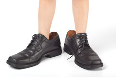 Big shoes to fill. Little kid wearing adult's shoes that are too big Royalty Free Stock Photography