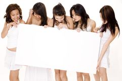 Big Sign #4. Five cute young women in white look down at a large white blank sign Stock Images