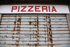 The big sign of Pizzeria with the gate closed Stock Image