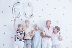 Big silver balloons. Seniors holding big silver balloons at their friend`s birthday party Royalty Free Stock Image