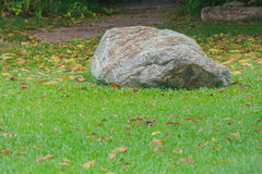 Big silver stone on green grass surrounded autumn leaves. Royalty Free Stock Photography