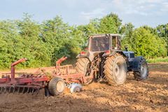 Big silver tractor with a red harrow disc cultivator in the field on a sunny day. The concept of work in a fields and agricultur. Big silver tractor with a red Royalty Free Stock Photo