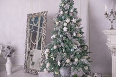 Big silver and white decorated christmas tree with gifts in luxury interior. New year at home.Christmas interior with royalty free stock image