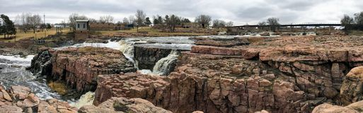 The Big Sioux River flows over rocks in Sioux Falls South Dakota with views of wildlife, ruins, park paths, train track bridge, tr. Views of the Big Sioux River Royalty Free Stock Photos