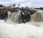 The Big Sioux River flows over rocks in Sioux Falls South Dakota with views of wildlife, ruins, park paths, train track bridge, tr. Views of the Big Sioux River Royalty Free Stock Photography