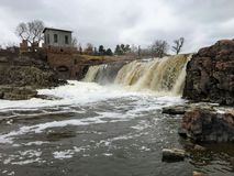 The Big Sioux River flows over rocks in Sioux Falls South Dakota with views of wildlife, ruins, park paths, train track bridge, tr. Views of the Big Sioux River stock image