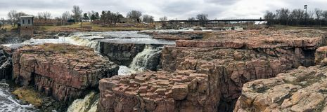 The Big Sioux River flows over rocks in Sioux Falls South Dakota with views of wildlife, ruins, park paths, train track bridge, tr. Views of the Big Sioux River Royalty Free Stock Photo