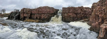 The Big Sioux River flows over rocks in Sioux Falls South Dakota with views of wildlife, ruins, park paths, train track bridge, tr. Views of the Big Sioux River stock photography