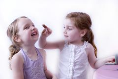 Big sister applying makeup to little sister. Siblings having fun playing with makeup Stock Photography