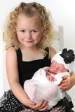 Big sister and baby. Beautiful blond girl, holding her newborn baby sister Stock Image
