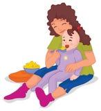 Big sister feeding the baby Stock Photo