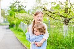 Big sister giving a hug to her toddler brother. Adorable children playing together on a nice summer day, outdoors Royalty Free Stock Images