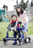 Big sister helping disabled brother walk. Big sister helping younger disabled brother to walk in his walker outside Stock Image