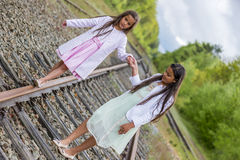 Big sister helping little sister. To balance on a railroad track Stock Photography