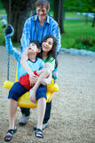 Big sister holding disabled brother on special needs swing at pl Royalty Free Stock Image