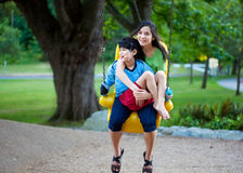 Big sister holding disabled brother on special needs swing at pl. Ayground in park. Child has cerebral palsy Stock Photo