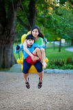Big sister holding disabled brother on special needs swing at pl Stock Images
