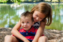 Big Sister Hugs Her Little Brother. A big sister sits with her little brother in her lap while she hugs him. She leans over and in adoration, she looks down at Royalty Free Stock Images