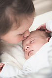 Big sister kissing her newborn brother Stock Image