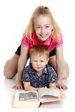 Big sister and little brother reading a book lying Royalty Free Stock Photo