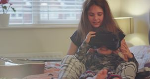 Big sister playing with her small brother in her bedroom she put a VR on her brothers for first time , little boy was stock video