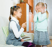 Big sister preaching little one. Annoying big sister preaching little one and shaking finger in apartment Royalty Free Stock Photos