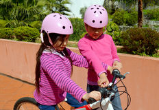 Big sister teaching sibling to ride Royalty Free Stock Images
