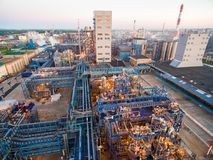 A huge oil refinery with metal structures, pipes and distillation of the complex with burning lights at dusk. Aerial. On a big site plant located distillation Stock Images