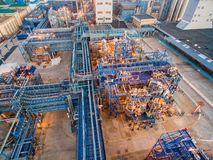 A huge oil refinery with metal structures, pipes and distillation of the complex with burning lights at dusk. Aerial Stock Photos