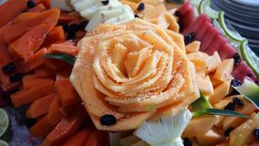 Flower made with fruit. Big size rose flower made with a piece of melon, flower over slices of fruits as papaya and watermelon with some slices of lemon, fruit stock images