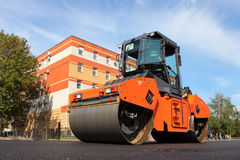 Big size steamroller flatten out the asphalt. Road roller is used to place the first layer of asphalt on a city street stock image