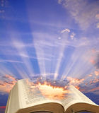 Big sky bible spiritual light. Photo of big blue sky with sunlight rays shining through the pages on open bible Stock Photography
