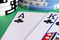 Big Slick. An ace and king of clubs with poker chips in the background stock photo