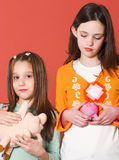 Big-small. Two girls holding they're toy banks Stock Image