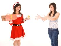 Big Or Small. A female dressed as santa tries to decide whether to give the big or small present to the same woman dressed casually with arms outstretched Stock Photo