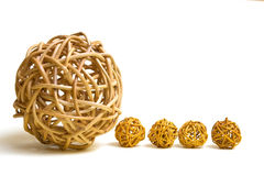 Big and small. Spheres of wicker placed in a row, a large and four small Stock Photography