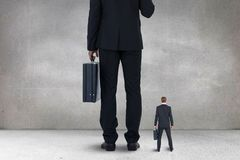 Big and small business men standing. Digital composite of Big and small business men standing stock images