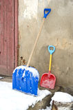 Big and small father and child snow shovels near wall Stock Photography