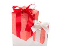 Big and small gift boxes. The big and small gift box decorated with a ribbon and a bow, isolated on white Stock Photos