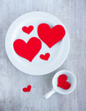 Big and small hearts on the white china dishes. Top view royalty free stock images