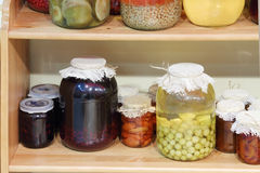 Big and small jars with jam, stewed and pickled mushrooms Royalty Free Stock Images
